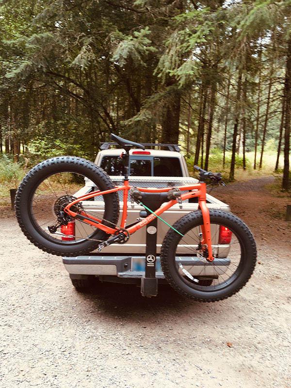 Orange Co-op fat tire bike on Thule rack on back of tan Ford Ranger